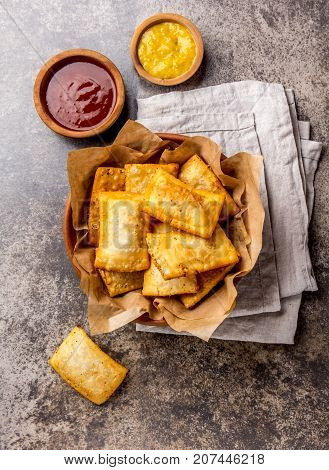 Fried cheese empanadas. Traditional Latin American snack in clay served bowl with chili sauce and mustard. Top view, stone background.