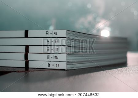 stack of several edition of luxury white magazine with gold strip at side