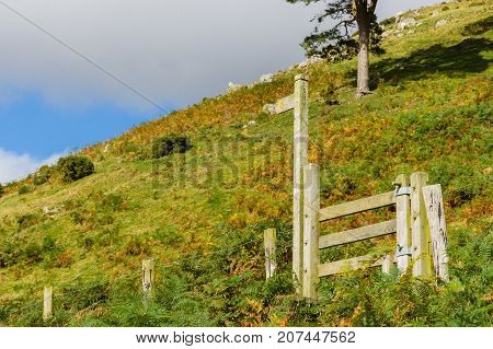 Rural sign post and wooden stile on a hiking trail leading up a mountain trail on in Wales UK with generous copy space