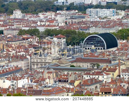 Aerial view of a cityscpae of downtown Lyon in France with plenty of red roofs and white old buildings including the opera and the city hall