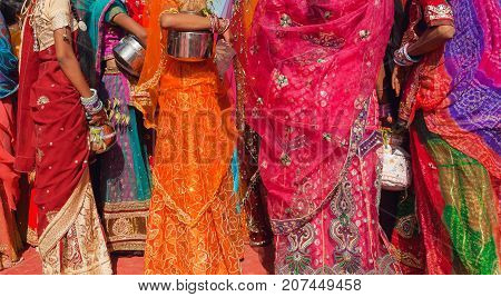 Beautiful crowd of colorfu women dressed traditional indian sari with patterns going for water with jars.