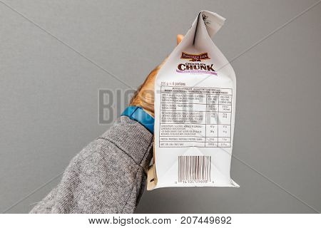 PARIS FRANCE - OCT 5 2017: Nutrition information in hand holding delicious Chocolate Chunk bag made by Pepperidge Farm against gray background