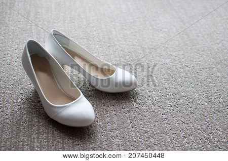 white wedding shoes for the bride on carpet