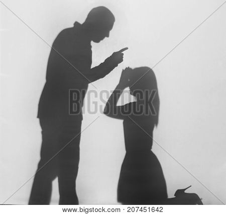 Silhouette of man shouting at his wife, on white background. Domestic violence concept