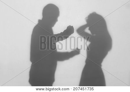 Silhouette of man hurting his wife on white background. Domestic violence concept