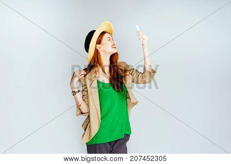 girl in hat smiling making selfie on white background