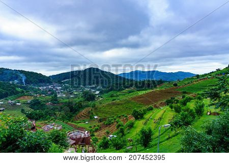 panorama dramatic view of valley with mist over the mountain and cloudy sky background in the morning Mon Cham Valley Chiangmai Thailand.Beautiful panorama view of mon cham valley with cloudy sky and mountain background in the morning. Chiangmai Thailand.