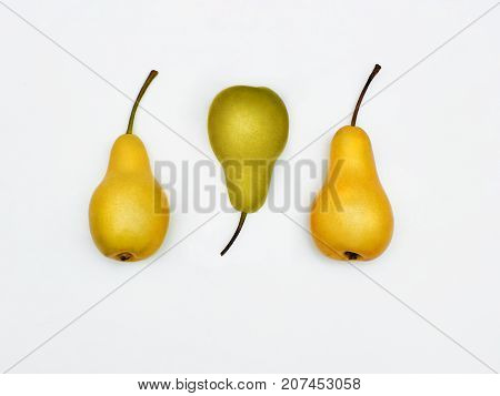 Two yellow pears and one green pear are lying in a row on white background Isolated seasonal fruit Flat lay