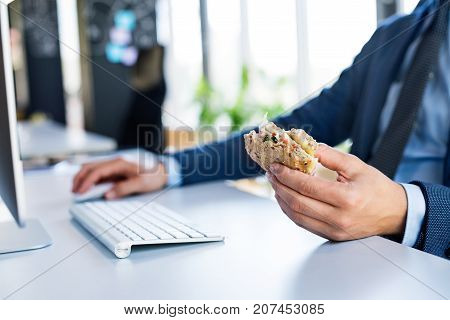 Unrecognizable young businessman in his office, sitting at the desk, computer in front of him, eating his lunch.