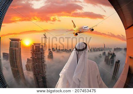 Arabian man watching plane flying over Dubai in United Arab Emirates