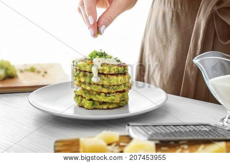 Woman decorating tasty broccoli pancakes at table
