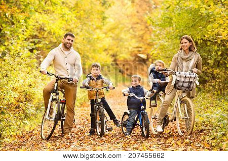 Beautiful young family with three sons in warm clothes cycling outside in autumn nature