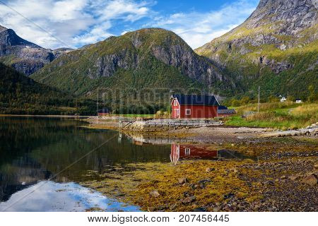 Traditional red rorbu cottages at the sea under the mountains on Lofoten islands in Norway.
