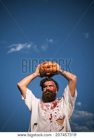 Halloween Man Holding Pumpkin Overhead On Blue Sky
