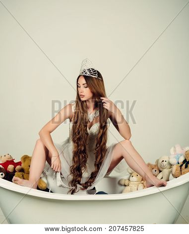Girl Sitting On Bath Tub On Grey Background.