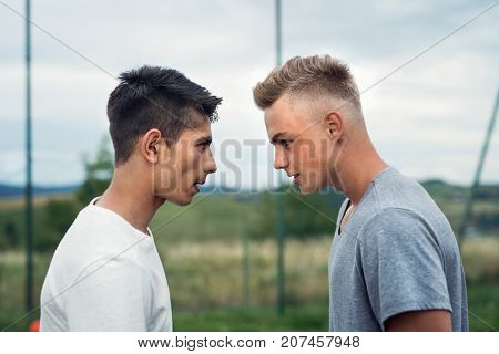 Two handsome teenage boys outdoors on playground looking at each other with hate, rivals accepting challenge.