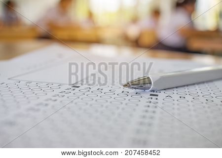 Close-up pen on optical form of standardized test with answers bubbled for examination or answer sheet Education concept selective focus.