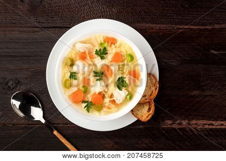 An overhead photo of a plate of chicken, vegetables, and noodles soup, shot from above on a dark rustic texture with slices of bread and a spoon, and a place for text