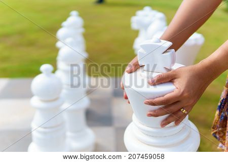 women hand moving big white wood chess on the chessboard floor with blurred black wood chess background.