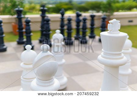 Close Up Of Big White Wood Chess On The Chessboard Floor With Black Wood Chess Background. Decision