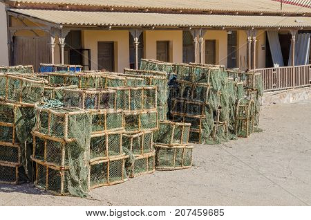 Many lobster or crayfish traps stacked in front of old building, Luderitz, Namibia, Southern Africa.