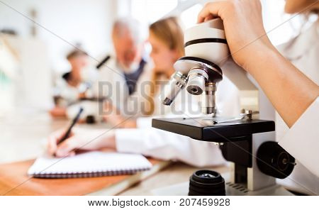 Unrecognizable high school student with microscope in laboratory during biology class.
