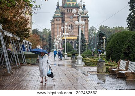 TIMISOARA ROMANIA - SEPTEMBER 21 2017: Old woman with an umbrella walking on the iconic Victory Square (Piata Victorei) the Metropolitan Cathedral (Catedral Mitropolitana) can be seen in the background