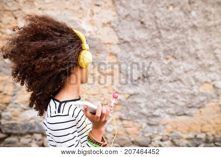 Beautiful african american girl with curly hair outdoors against concrete wall, holding smart phone, wearing yellow headphones, listening music and eating lollipop.