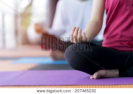 Young couple people doing yoga meditation on yoga mat at indoor studio - Yoga Concept