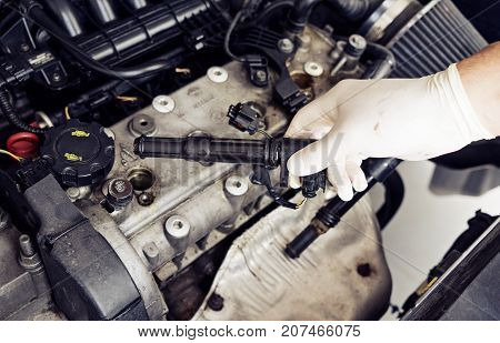 A man's hand will check the spark plugs in the car close up, toned blue