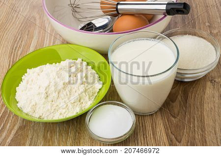 Whisk And Eggs In Bowl And Other Ingredients For Pancakes