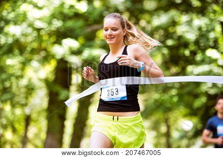 Beautiful young woman running the race crossing the finish line.
