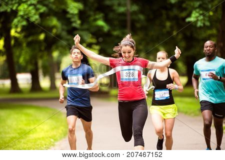 Beautiful young woman running in the crowd crossing the finish line.