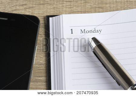 Μetal pen on a calendar with the page showing the first day of the month/week and a smartphone in a setting goals concept