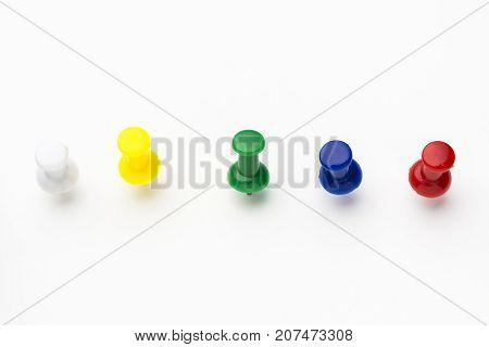 Five colored push pins on white background
