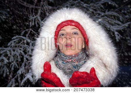 Portrait of young attractive girl in red hat and mittens and in fur coat made of artificial fur, is sending air kiss and looking at camera on winter snowy evening.