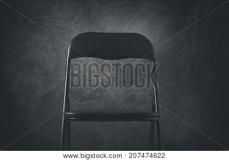Single black chair on a stage against a dark background.