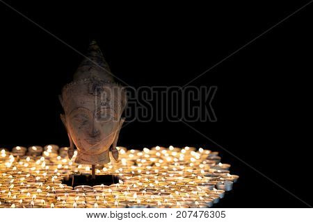 Enlightenment. Spiritual image of serene buddha head illuminated by tealight candles. Beautiful Buddhism image with black background and copy space.