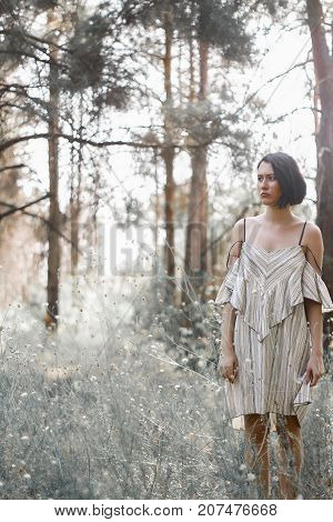 fashion styling girl is emotional. she is dressed in white with black stripes dress.forest with trees. girl is angry. woman in wonderland