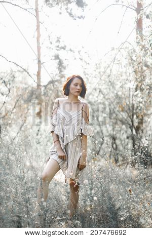 fashion styling girl is emotional. she is dressed in white with black stripes dress.forest with trees. Woman in wonderland.