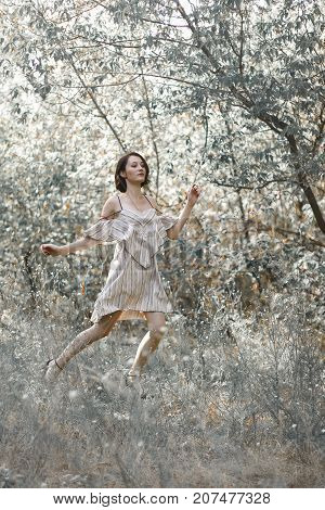fashion styling girl is emotional. she is dressed in white with black stripes dress.forest with trees. girl in dinamic. model is running or jumping. woman in wonderland