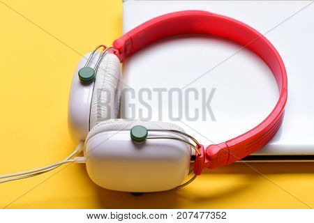 Earphones Made Of Plastic With Computer On Orange Background