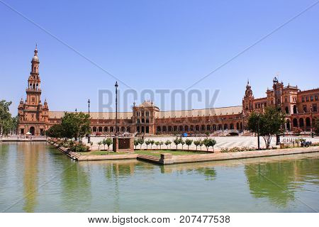 Plaza de Espana, also known as Spain Square, in Seville. Historical medieval architecture buildings with small waterfront on summer day scene. Famous spanish travel landmark in Andalucia region.