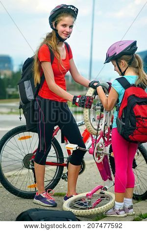Bikes bicyclist girl. Children girls wearing helmet repair bicycle. Kids travel unaccompanied.