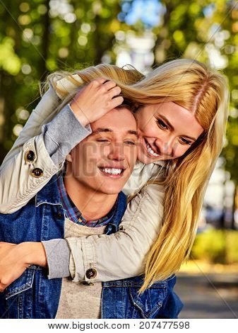 Walking bike of couple in park and kissing. Summer friends walk outdoor. First date of two young people in good weather day. First love.