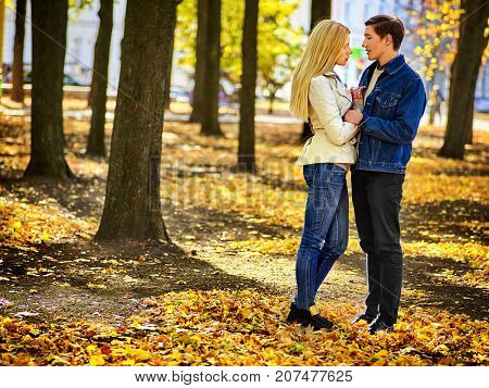 Spring couple walking park and kissing. Summer friends walk outdoor. First date and kiss of two young people in good weather day. Girl flirts with guy, touching his nose. Man in good mood. First love.
