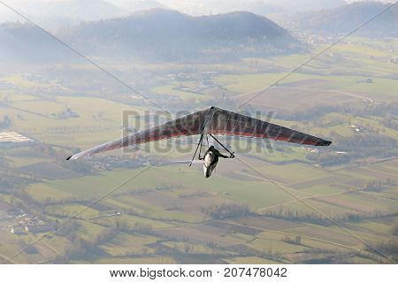 extreme sport with a man flying with his hang glider above the plain