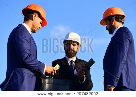 Board of architects with interested faces in suits and helmets take notes and hold money. Deal and construction concept. Builders make bargain. Workers and engineer hold meeting on blue sky background