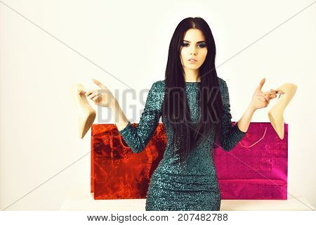 pretty woman or sexy cute girl with bright makeup on adorable face with long brunette hair in sequins green dress with pink and orange shopping bags packages shoes isolated on white background