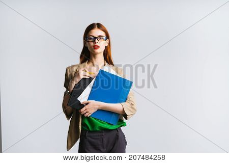girl secretary with a serious facial expression holds a file